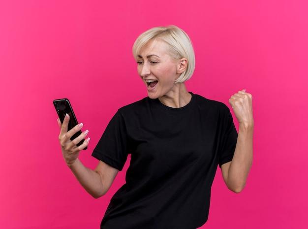 Freudige blonde slawische frau mittleren alters, die das handy betrachtet, das ja geste lokalisiert auf rosa wand tut
