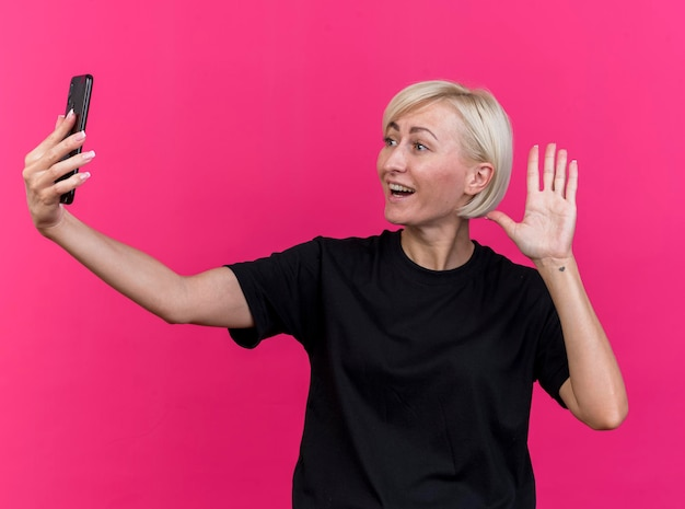 Freudige blonde slawische frau mittleren alters, die handy hält und betrachtet, das hi geste lokalisiert auf rosa wand tut