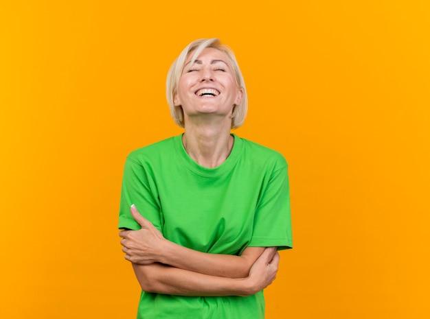 Freudige blonde slawische frau mittleren alters, die mit geschlossener haltung steht und mit geschlossenen augen lacht, lokalisiert auf gelbem hintergrund mit kopienraum