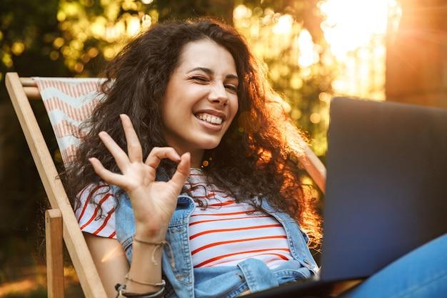 Freudige brünette frau, die ok oder in ordnung zeichen zeigt, während sie im liegestuhl während der ruhe im park am sonnigen tag sitzt und mit silbernem laptop