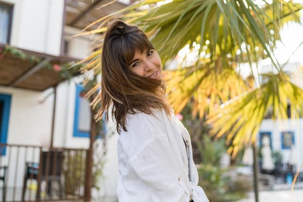 Freudige brünette frau, die sommertag erfreut. weiße bluse tragen. palmen auf hintergrund.