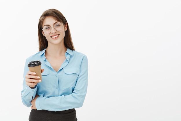 Freudige brünette geschäftsfrau, die im studio mit kaffee aufwirft