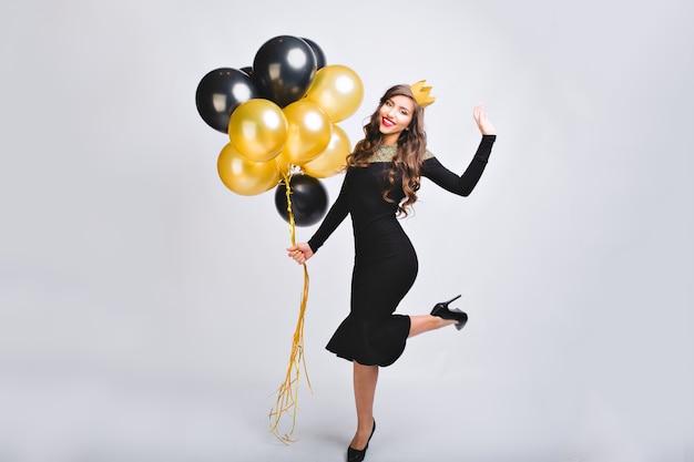 Freudige charmante junge frau im luxuriösen eleganten modekleid auf den fersen, die neujahrsparty auf weißem raum feiern.