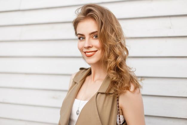 Freudige charmante junge frau mit natürlichem make-up mit lockigem blondem haar in einer stilvollen weste lächelt