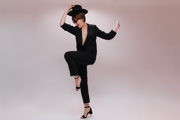 Freudige dame im anzug nimmt hut ab und springt auf weißem hintergrund. hübsche frau in der schwarzen jacke und in der hose tanzen auf isoliertem hintergrund