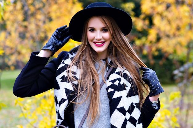 Freudige dame im schwarzen hut und in den handschuhen, die mit langen haaren mit wald auf hintergrund spielen. schönes mädchen, das mantel und stilvollen schal trägt, der während des spaziergangs im herbstpark lächelt.