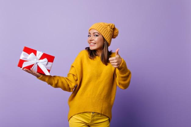 Freudige dame im stilvollen gelben hut, der mit geburtstagsgeschenk tanzt. lachendes kaukasisches mädchen, das neujahrsgeschenk auf lila hält.