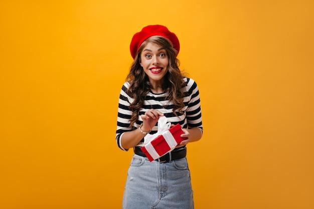 Freudige dame in der roten baskenmütze hält geschenkbox auf orange hintergrund. schöne frau mit lockigem haar im gestreiften pullover und im jeansrock, der in kamera schaut.