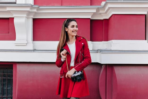 Freudige dame in lässigen roten kleidern, die jemanden mit kamera warten
