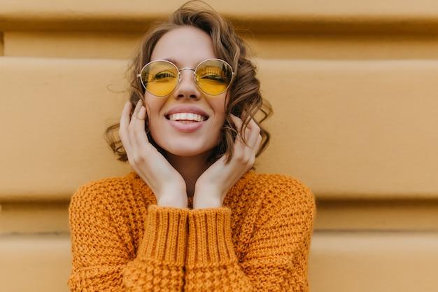 Freudige dame mit blasser haut, die fotoshooting im freien genießt und lächelt