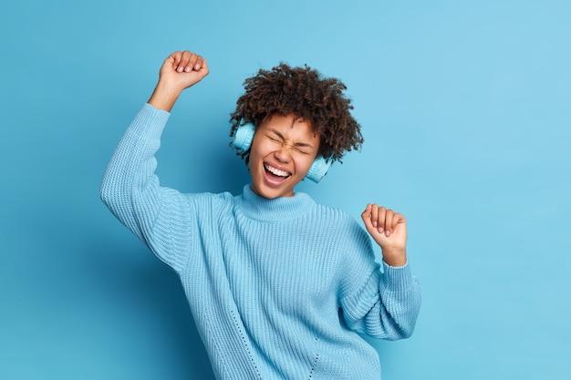 Freudige dunkelhäutige lockige frau tanzt sorglos hebt die arme fühlt sich optimistisch an trägt stereokopfhörer genießt lieblingsmusik trägt strickpullover