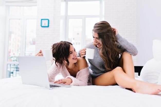 Freudige entspannungszeit zusammen von zwei jungen attraktiven frauen, die spaß auf weißem bett haben. schöne modelle in wollpullovern mit nackten beinen, tee trinken, im internet surfen, den morgen genießen.
