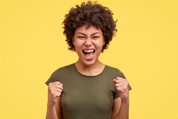 Freudige ethnische junge frau mit afro-frisur, ballt die fäuste mit triumph, erreicht großartig