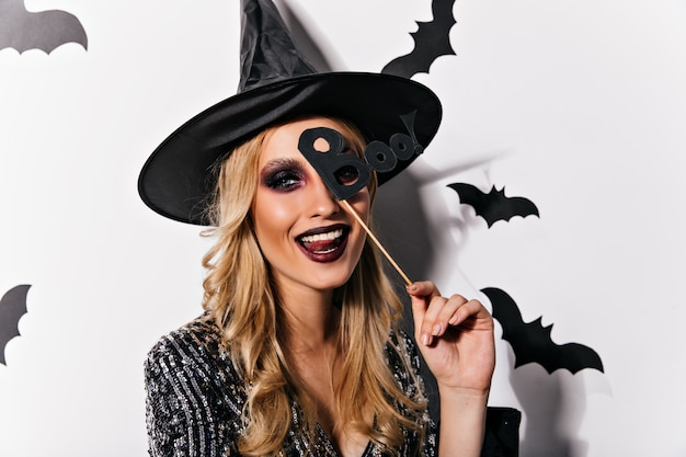 Freudige europäische frau, die spielerisch in halloween aufwirft. entzückende junge hexe mit schwarzem make-up, das glück ausdrückt.
