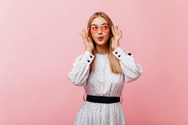 Freudige europäische frau in der eleganten brille, die mit vergnügen aufwirft. innenporträt des ekstatischen weiblichen modells im weißen kleid.
