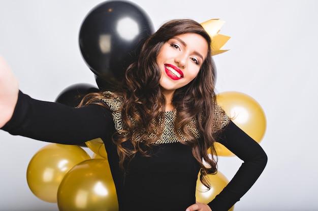 Freudige frau des selfie-porträts mit langen lockigen brünetten haaren, gelber krone, schwarzem luxuskleid. neujahr feiern, geburtstagsfeier, spaß mit goldenen und schwarzen luftballons.