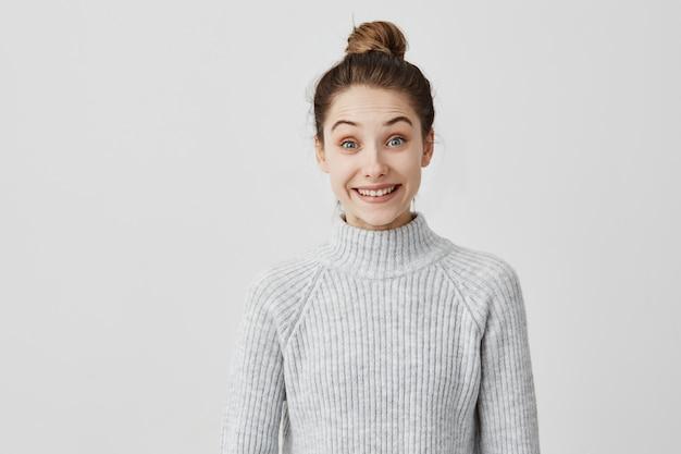 Freudige frau, die im lässigen grau mit großem lächeln aufwirft. brünette produzentin mit haaren im brötchen, die vor glück leuchten. medienkonzept