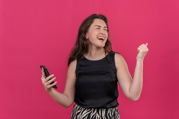 Freudige frau, die schwarzes unterhemd trägt, hören musik vom telefon auf rosa wand
