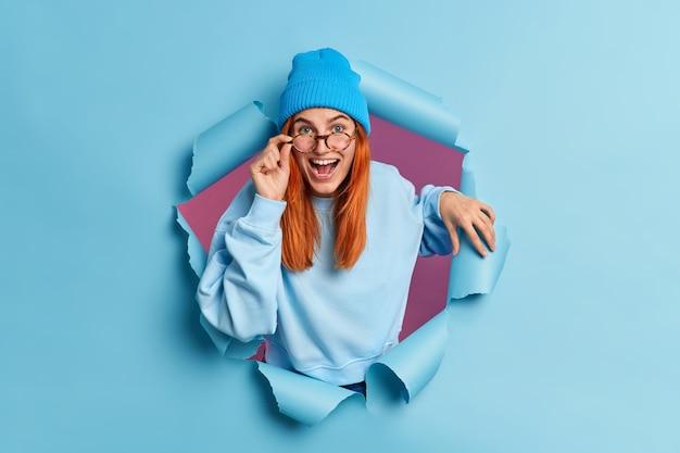 Freudige frau hat rotes haar lächelt breit hat fröhlich neugierigen ausdruck hält hand auf brille lacht positiv gekleidet in blaue kleidung bricht durch papierloch
