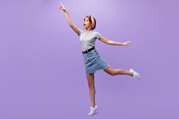 Freudige frau im grauen t-shirt und im rock, der einen isolierten hintergrund aufwirft. charmantes schönes mädchen im sommer modischen outfit springen.