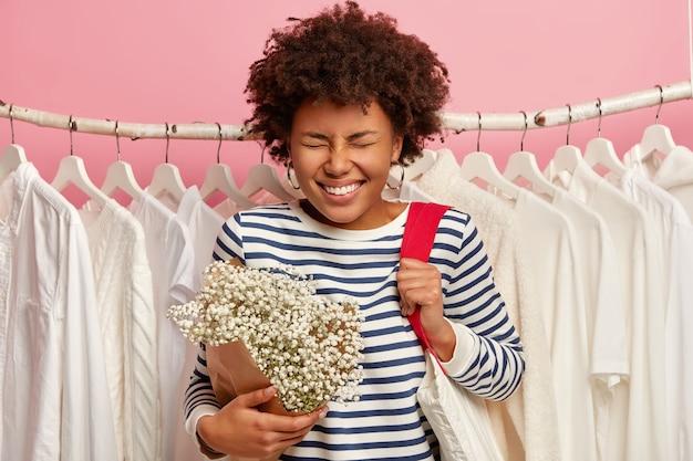 Freudige frau mit afro-frisur, lacht glücklich, trägt einkaufstasche, schöne blumen, steht gegen weiße kleidung im schrank auf kleiderbügeln, froh, im modegeschäft zu sein. emotionen und verkaufskonzept