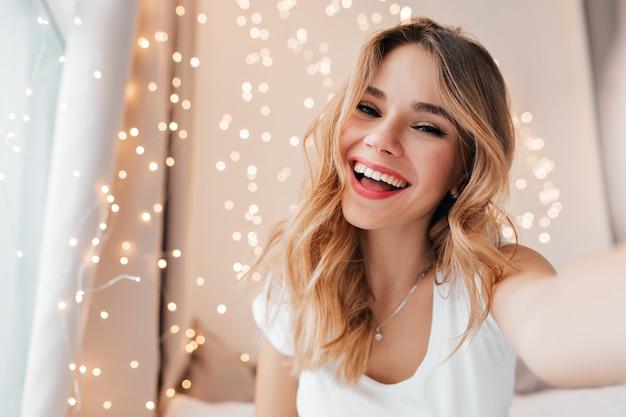 Freudige frau mit aufrichtigem lächeln, das in ihrem zimmer aufwirft. blondes kaukasisches mädchen, das glück ausdrückt