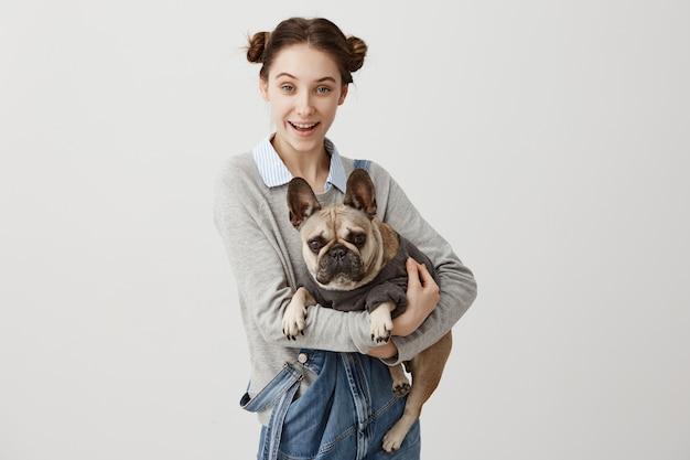 Freudige frau mit doppelbrötchen, die französische bulldogge in ihren händen halten, die sorge und verantwortung fühlen. großartige freunde, mensch und hund, die freude daran haben, zu hause zusammen zu spielen. freundschaftskonzept