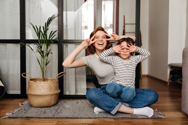 Freudige frau und ihre tochter haben spaß im wohnzimmer und zeigen zeichen des friedens.