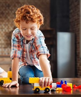 Freudige freizeitbeschäftigung. aufgeregter kleiner junge in freizeitkleidung, der breit grinst, während er auf einem tisch sitzt und zu hause mit einem gebauten auto spielt.