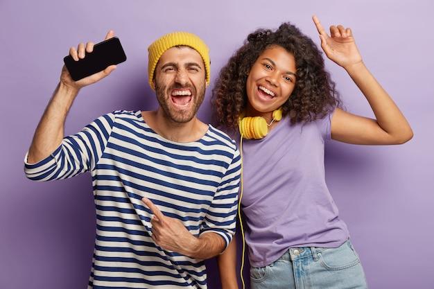 Freudige gemischte rasse junge frau und mann haben spaß und tanz, hören musik über handy-anwendung, tragen kopfhörer, in freizeitkleidung gekleidet
