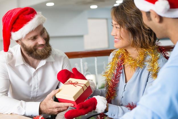 Freudige geschäftskollegen, die geschenke austauschen