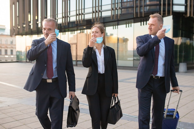 Freudige geschäftsleute, die gesichtsmasken abnehmen, während sie mit gepäck im freien von hotel- oder bürogebäuden gehen. vorderansicht. geschäftsreise und ende des epidemiekonzepts