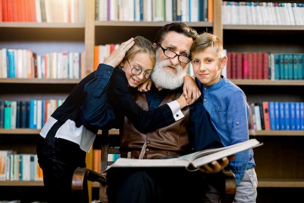 Freudige glückliche enkelin und enkel umarmen ihren hübschen bärtigen alten großvater, während sie gemeinsam über dem großen bücherregal mit verschiedenen büchersammlungen ein buch lesen