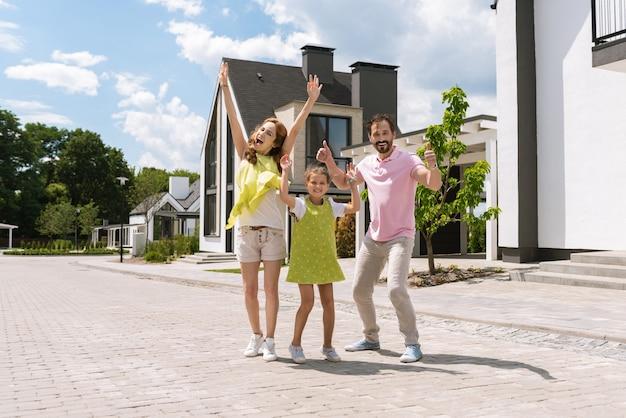 Freudige, glückliche familie, die ihre hände hochhält und gleichzeitig ihre positiven gefühle zeigt
