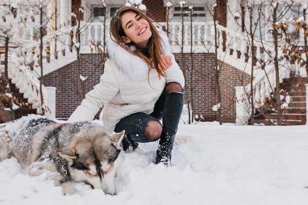 Freudige glückliche junge frau, die spaß mit niedlichem husky hund im schnee auf straße hat. fröhliche stimmung, schneereiche winterzeit, schöne haustiere, echte freundschaft.