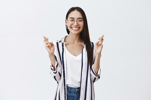Freudige glückliche und sorglose frau in brille und gestreifter bluse, die freudig mit geschlossenen augen lächelt, verträumt und begeistert ist, während sie mit gekreuzten fingern die hände hebt und sich etwas wünscht