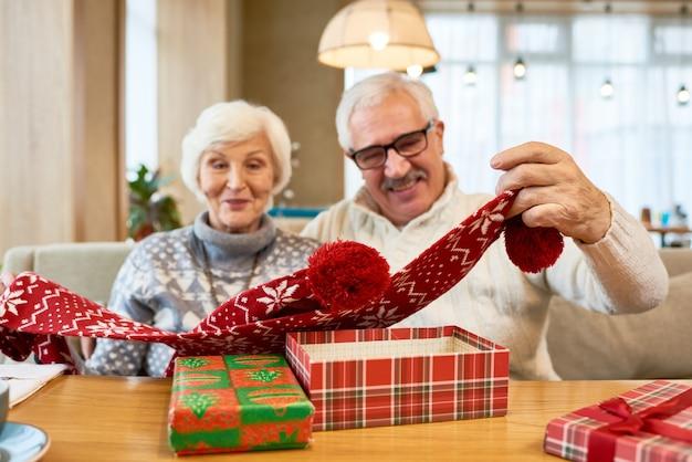 Freudige großeltern, die weihnachtsgeschenke am tisch öffnen