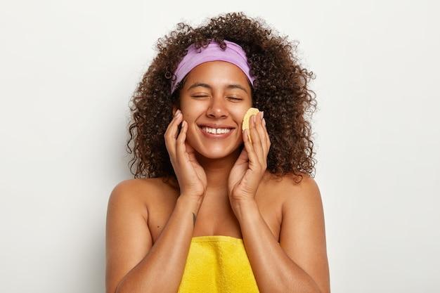 Freudige hübsche frau mit afro-haarschnitt, wischt gesicht mit rundem kosmetischen schwamm ab, entfernt make-up, hat natürliche schönheit, weras stirnband