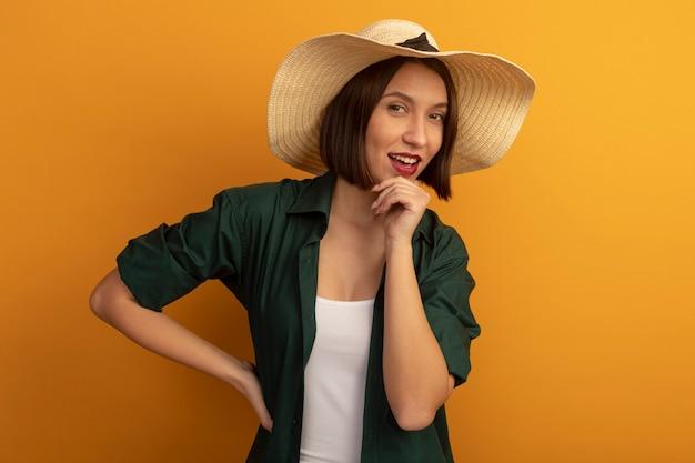 Freudige hübsche frau mit strandhut legt hand auf kinn und schaut vorne isoliert auf orange wand