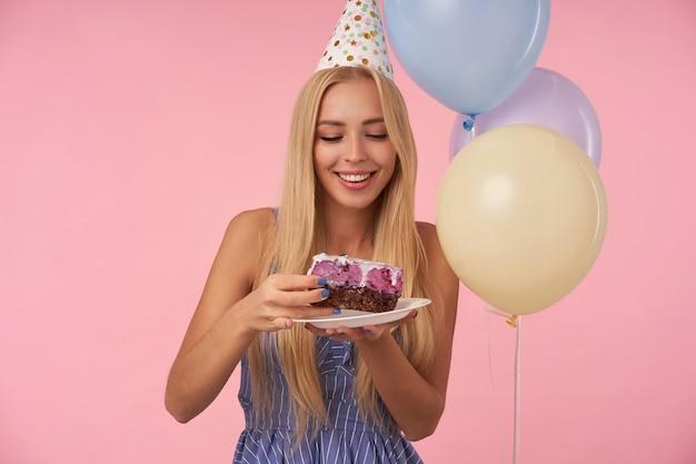 Freudige hübsche junge blonde dame in festlichen kleidern und kegelhut, die feiertagstorte essen, über rosa hintergrund und mehrfarbigen heliumballons stehend, ihre angenehmen gefühle zeigend