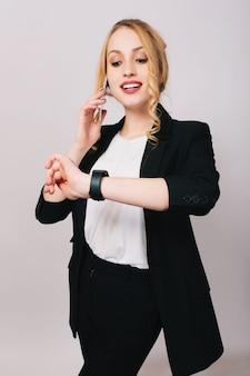 Freudige hübsche junge geschäftsfrau im büroanzug, die am telefon spricht, lächelt und auf uhr schaut. fröhliche stimmung, glücklich, erfolgreich, arbeiter, isoliert, korporativ