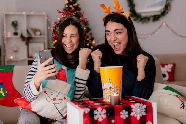 Freudige hübsche junge mädchen halten fäuste und schauen auf das telefon, das auf sesseln sitzt und die weihnachtszeit zu hause genießt