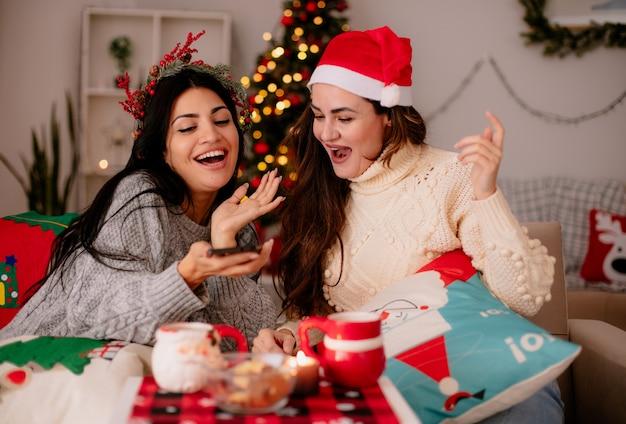 Freudige hübsche junge mädchen mit weihnachtsmütze schauen auf telefon, das auf sesseln sitzt und weihnachtszeit zu hause genießt