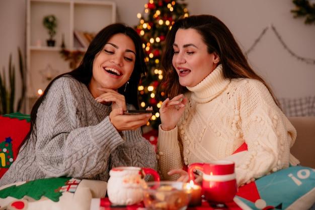 Freudige hübsche junge mädchen schauen auf telefon, das auf sesseln sitzt und weihnachtszeit zu hause genießt