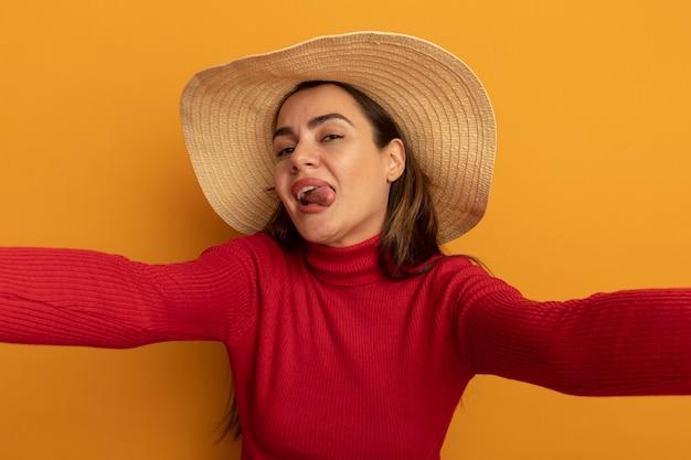 Freudige hübsche kaukasische frau mit strandhut ragt zunge heraus