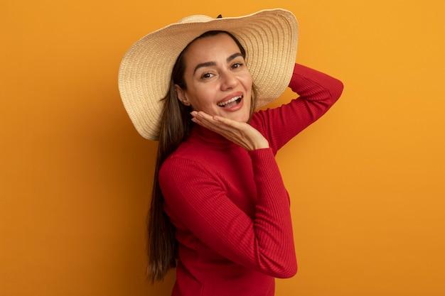 Freudige hübsche kaukasische frau mit strandhuthand auf gesicht und betrachtet kamera auf orange