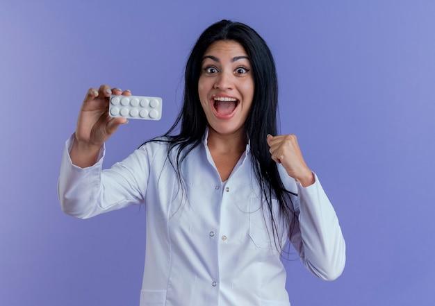 Freudige junge ärztin, die medizinische robe trägt, die packung der medizinischen tabletten zeigt und faust ballt