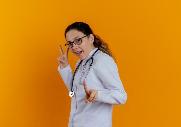 Freudige junge ärztin, die medizinische robe und stethoskop mit brille trägt, die friedensgesten lokalisiert zeigt
