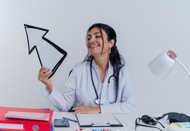 Freudige junge ärztin, die medizinische robe und stethoskop trägt, sitzt am schreibtisch mit medizinischen werkzeugen, die pfeilmarkierung halten und betrachten, die zur seite lokalisiert zeigt