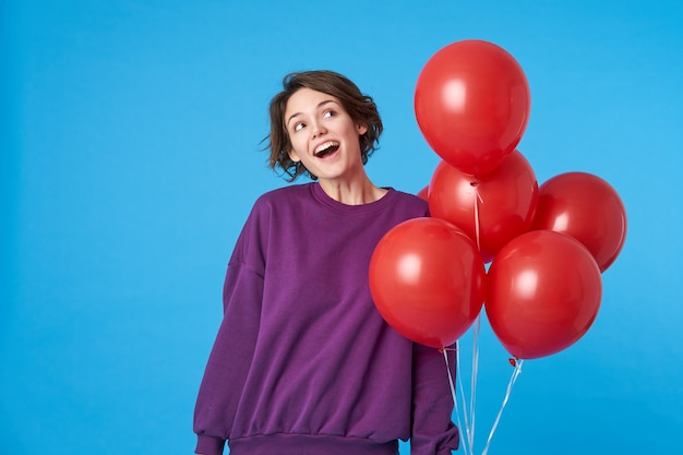 Freudige junge attraktive brünette frau gekleidet in lila sweatshirt, das luftballons hält